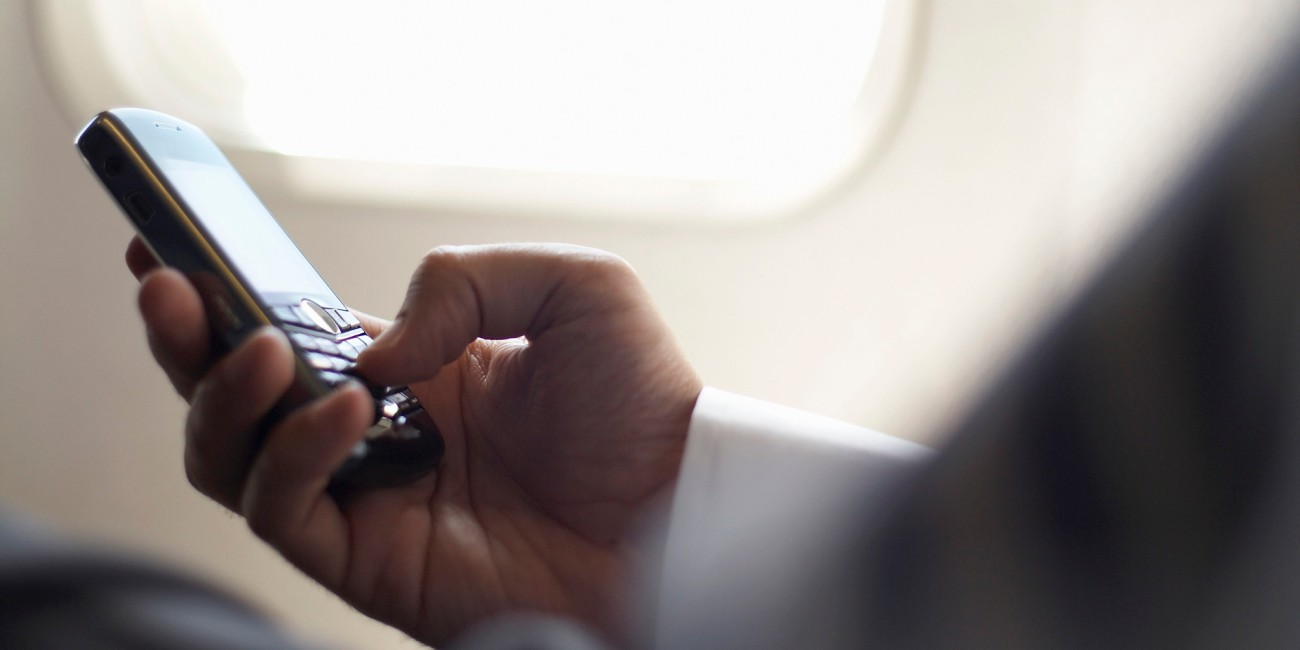 Close-up on hands of business man, sitting in airplane, holding mobile phone